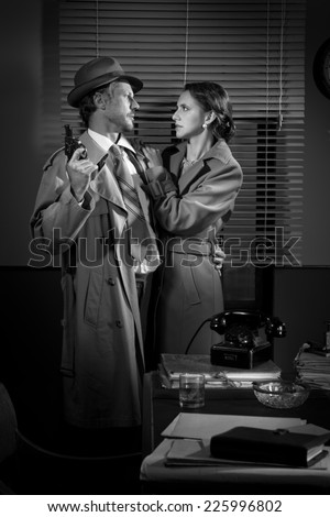 Passionate vintage couple embracing in detective's office holding a gun.