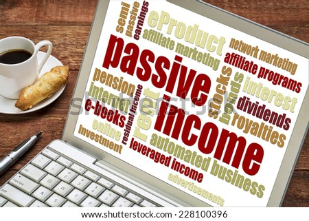 passive income word cloud  on a laptop with a cup of coffee - stock photo