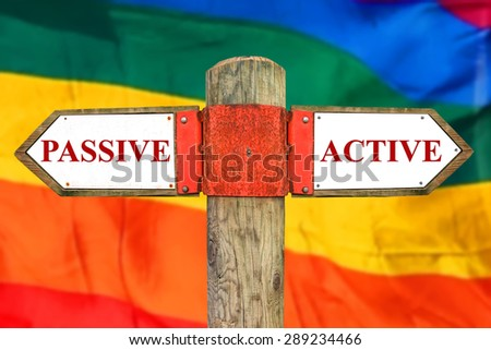 Passive versus Active messages - Wooden signpost with two opposite arrowson on the blurred rainbow gay pride flag fluttering background.  - stock photo
