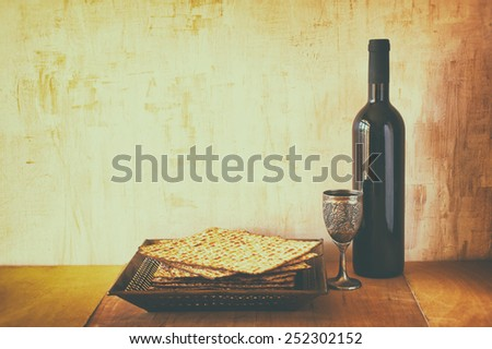 Passover background. wine and matzoh (jewish holiday bread) over wooden board. image is filtered with retro faded style - stock photo