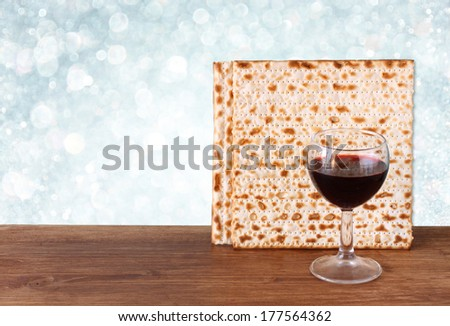passover background. wine and matzoh over wooden table - stock photo
