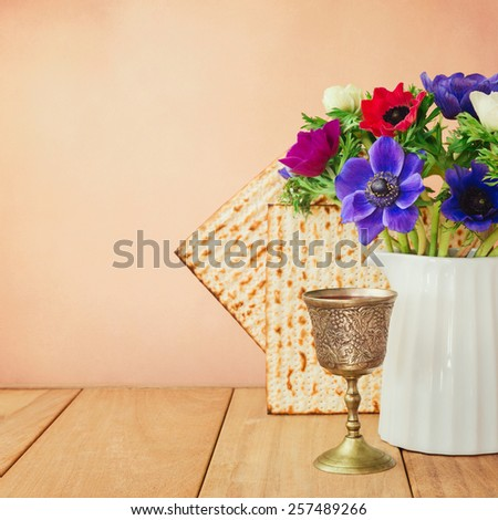 Passover background with matzo, wine and flowers on wooden table. Retro filter effect - stock photo