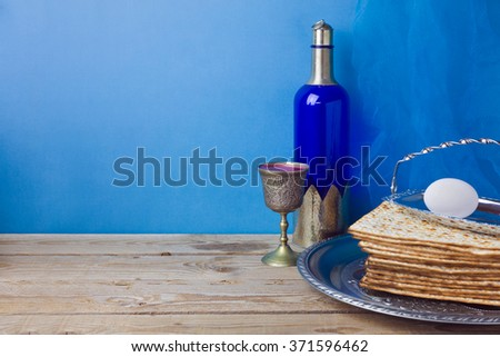 Passover background with wine, matzoh and egg over blue wall - stock photo