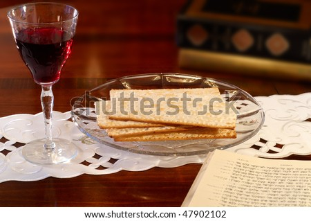 Passover elements of wine and matzoh on a table with Hebrew Old Testament open to the Passover passage in Exodus - stock photo