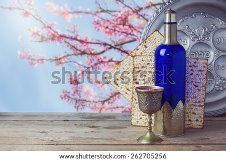 Passover matzo and wine on wooden vintage table over blossom tree background. Seder plate with hebrew text says bone and  lettuce. - stock photo