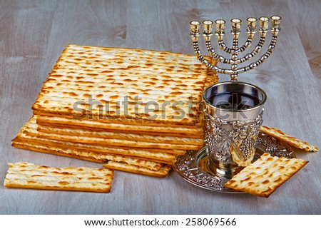 passover matzo with kiddush cup of wine on wooden table - stock photo