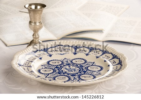 Passover Plate on white linen table cloth with Kiddush cup and Haggadah - stock photo
