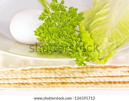Passover seder plate and matza. Close up of three covered matzas under a ceramic seder plate with hard boiled egg, parsley, and romaine lettuce leaf. - stock photo