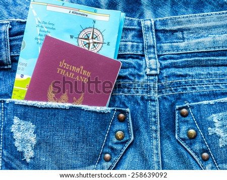 Passport book and world map in blue jeans pocket/ traveling concept - stock photo