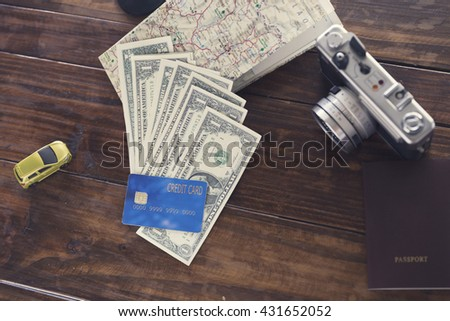 passport, credit card, banknote, camera,map, car figurine on wooden table for use as traveling concept (vintage tone and selected focus)