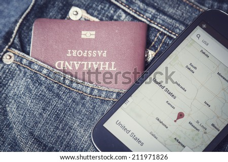 Passport in denim jeans pocket and map in smartphone, Vintage color - stock photo