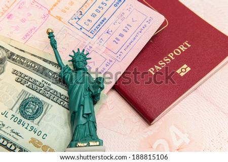 Passport, money and small statue of liberty - stock photo