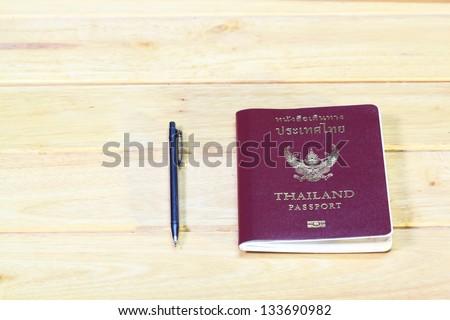 Passport on wood and pen - stock photo
