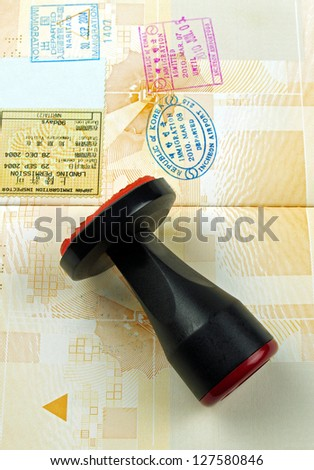passport stamps and stamping tool - stock photo