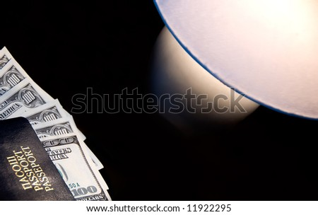 Passport with dollars on the night table with lamp - stock photo
