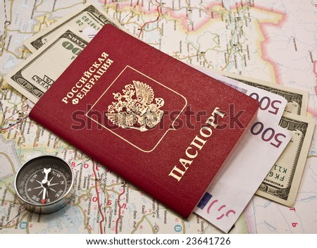 Passport with the money on a map and compass - stock photo