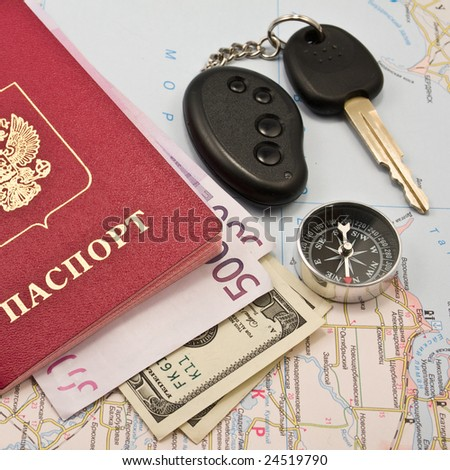 Passport with the money on a map, Car key,  keychain   and compass - stock photo