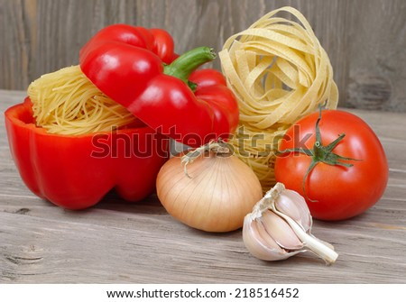 Pasta and fresh vegetables on a wooden background.