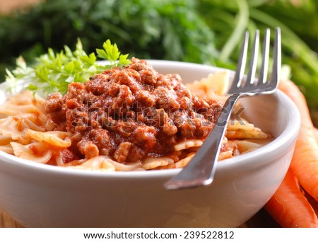 Pasta Bolognese in a bowl with ingredients around - stock photo