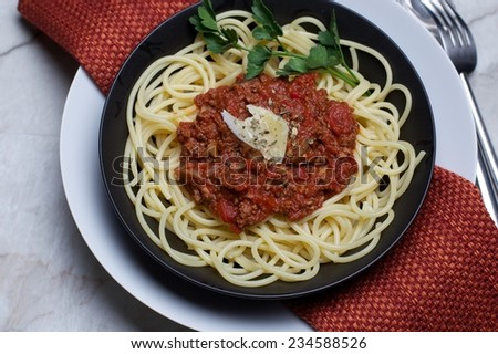 Pasta Bolognese in Black Bowl, with Red Napkin, on Marble Table - stock photo