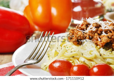 Pasta bolognese in the white plate on the wooden table with vegetables