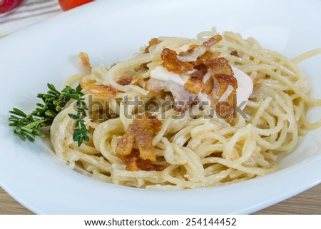 Pasta carbonara with sauce and bacon served thyme