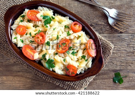 Pasta casserole with cherry tomatoes, cheese and herbs over rustic wooden background