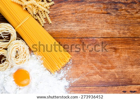 Pasta composition with flour and egg lying on wooden rustic table top view