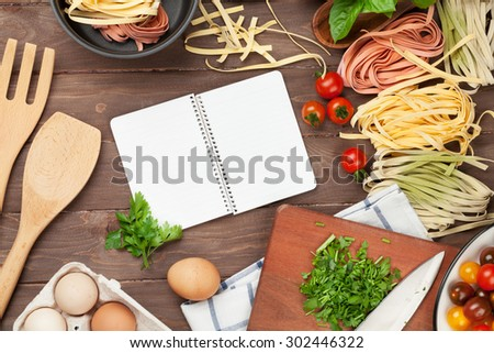Pasta cooking ingredients and utensils on wooden table. Top view with notepad for copy space - stock photo