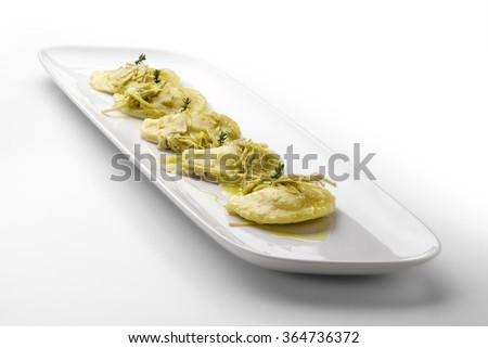 Pasta dish Potato ravioli stuffed with lobster and artichokes - stock photo
