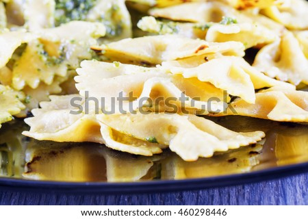 Pasta farfalle al pesto over reflecting plate, horizontal image - stock photo