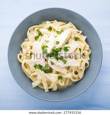 Pasta fettuccine alfredo with chicken, parmesan and parsley on blue wood background top view. Italian cuisine. - stock photo