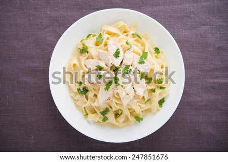 Pasta fettuccine alfredo with chicken, parmesan and parsley on dark background top view. Italian cuisine. - stock photo