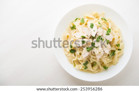 Pasta fettuccine alfredo with chicken, parmesan and parsley on white background top view. Italian cuisine. Space for text. - stock photo