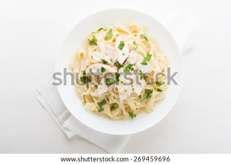 Pasta fettuccine alfredo with chicken, parmesan and parsley on white wooden background top view. Italian cuisine. - stock photo