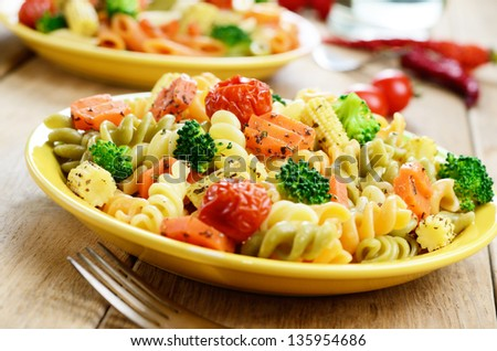 Pasta fusilli salad with broccoli carrot corn and tomatoes on the kitchen table - stock photo
