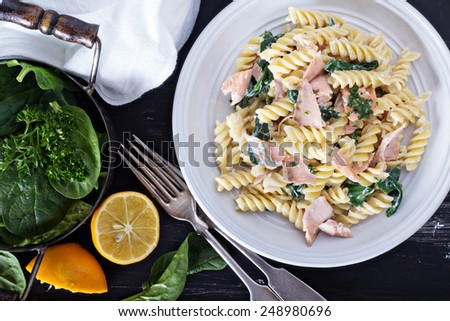 Pasta fusilli with baked salmon, sour cream and spinach - stock photo