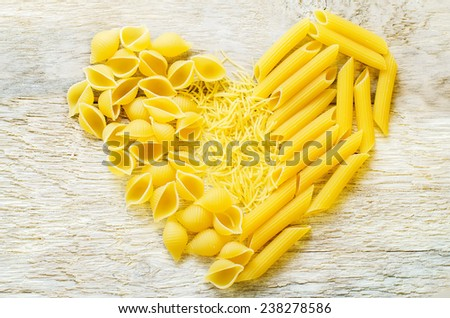 pasta in the form of hearts on the white wood background. tinting. selective focus - stock photo