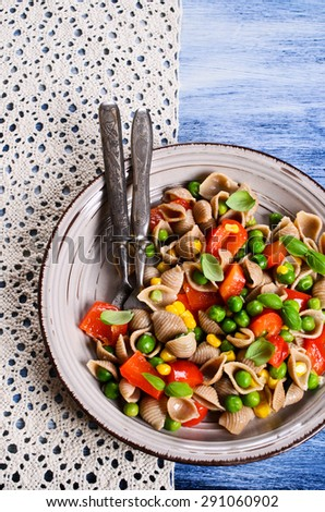 Pasta in the shape of seashells from rye flour with vegetables - stock photo