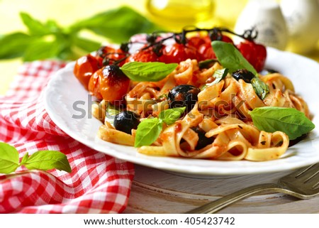 Pasta in tomato sauce with olives,basil and grilled cherry tomatoes on a yellow background. - stock photo