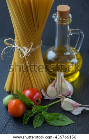 Pasta ingredients. Ingredients for cooking Italian pasta - spaghetti, tomatoes, basil, oil and garlic. Italian food. Side view of spaghetti tied with rope, stand on the table - stock photo