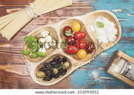 Pasta Ingredients. Ingredients for Italian Spaghetti. Italian Pasta spaghetti with tomatoes, olives, mozzarella and Parmesan cheese and basil. Ingredients for cooking over rustic table. - stock photo