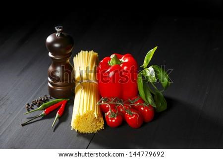 Pasta ingredients on black table, italian cuisine concept - stock photo