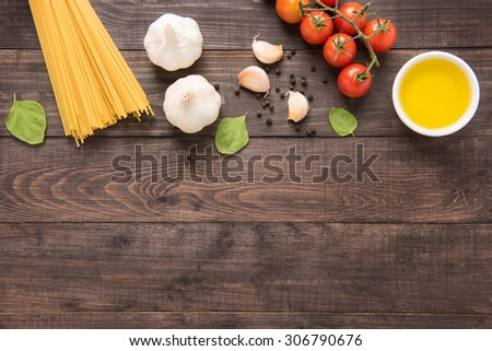 Pasta ingredients. tomato, garlic, pepper, oil and mushroom on wooden background. - stock photo