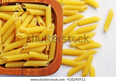 Pasta. Italian penne rigate macaroni pasta. Raw penne pasta. Raw pasta in wooden bowl on white background. - stock photo