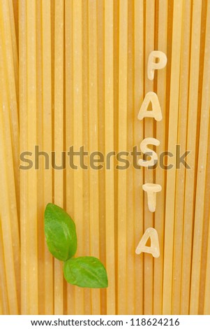 Pasta letters on spaghetti background with basil leaf - stock photo