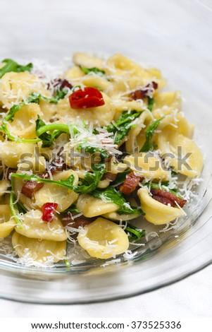 pasta orecchiette with ruccola and bacon - stock photo