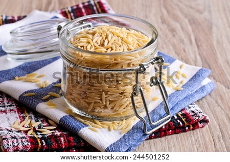 Pasta Orzo not prepared. Is in a glass jar. - stock photo