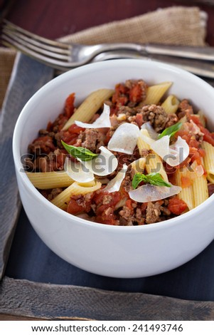 Pasta penne Bolognese with fried bacon and spices - stock photo