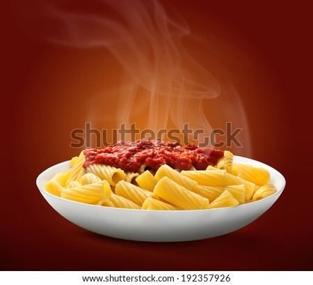 pasta Penne in plate on dark red background - stock photo
